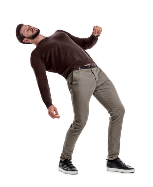 A bearded fit man in casual clothes stands with his back deeply bent backwards on a white background. A bearded fit man in casual clothes stands with his back deeply bent backwards on a white background. Loss of position. Falling man. Risky move. bending over backwards stock pictures, royalty-free photos & images