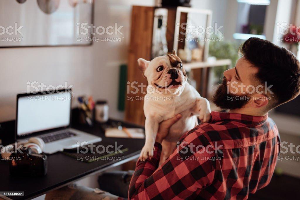 Bärtige Freiberufler arbeiten von zu Hause aus seinen niedlichen Hund mit gedrückter – Foto