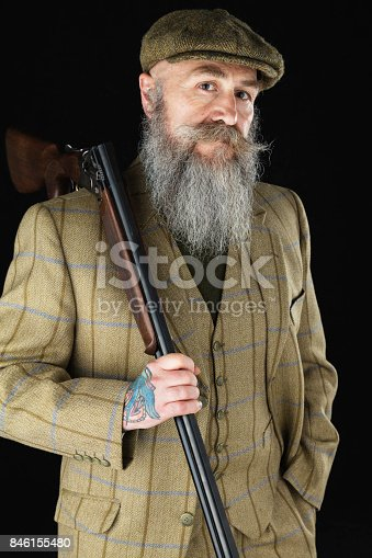 A bearded country gentleman wearing a 3-piece suit and cap and carrying a shotgun.