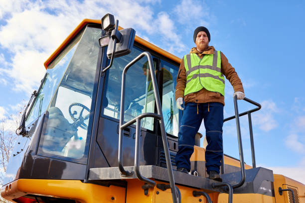 Bearded Gold Miner Posing on Truck Low angle portrait of bearded worker standing on heavy yellow truck posing looking at camera against cold blue sky frontier field stock pictures, royalty-free photos & images