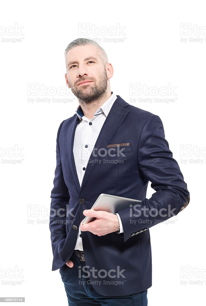 Bearded grey hair businessman holding a digital tablet Portrait of elegant bearded grey hair businessman standing against white background, holding a digital tablet in hands, looking up. Studio shot, one person.  2015 Stock Photo