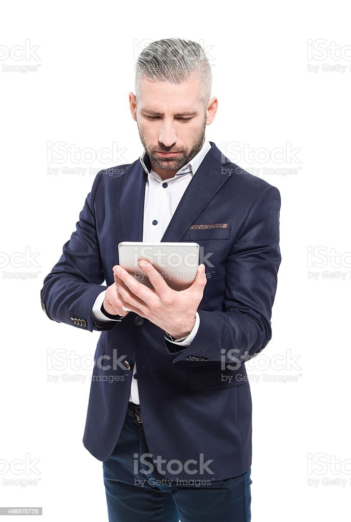 Bearded grey hair businessman using a digital tablet Portrait of elegant bearded grey hair businessman standing against white background and using a digital tablet. Studio shot, one person.  2015 Stock Photo