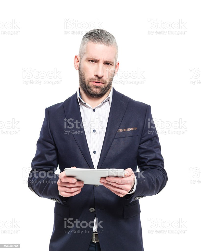 Bearded grey hair elegant businessman holding digital tablet Portrait of elegant bearded grey hair businessman wearing suit, holding a digital tablet in hand, looking at camera with pensive facial expression. Studio shot, one person, isolated on white. Adult Stock Photo