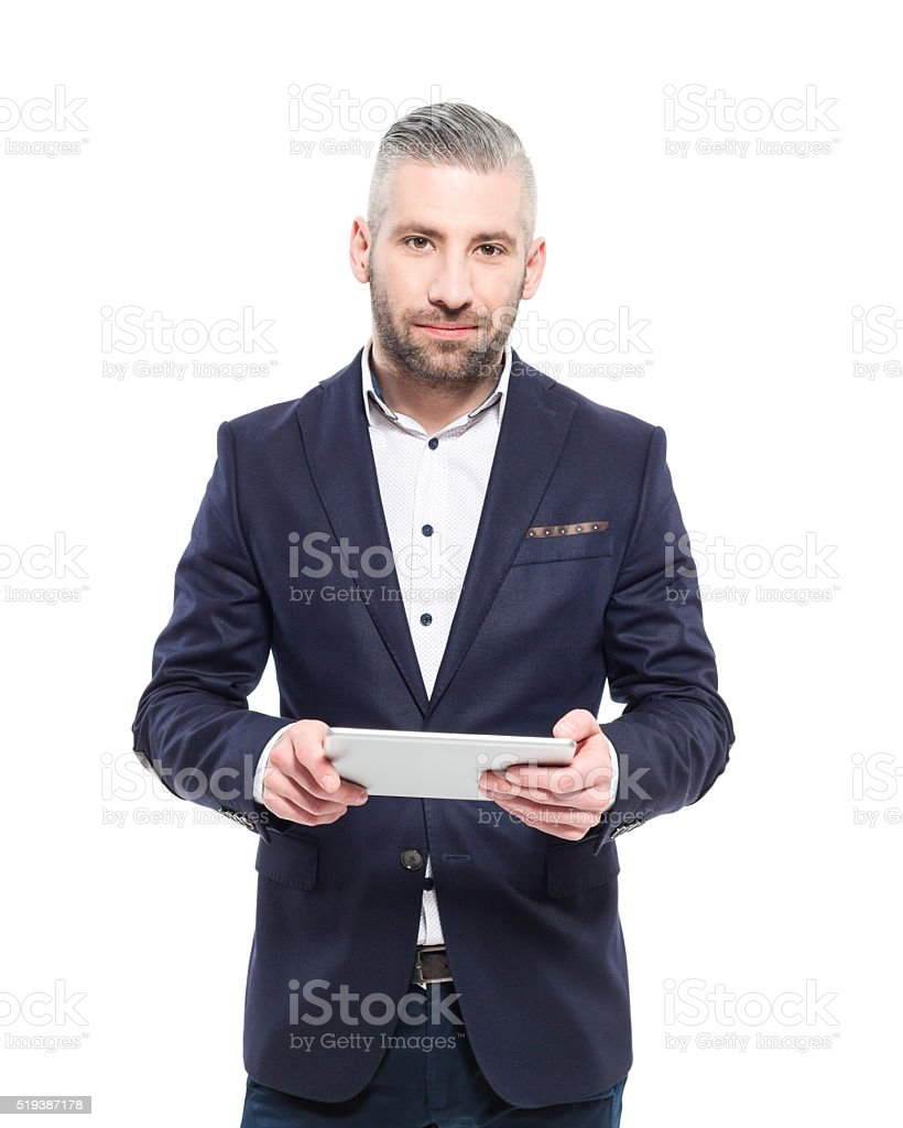 Bearded grey hair elegant businessman holding digital tablet Portrait of elegant bearded grey hair businessman wearing suit, holding a digital tablet in hand, looking at camera. Studio shot, one person, isolated on white. Adult Stock Photo