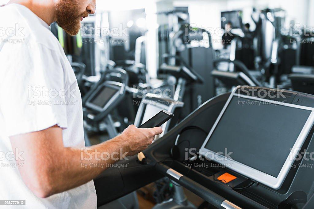 Bearded guy in gym at treadmill stock photo