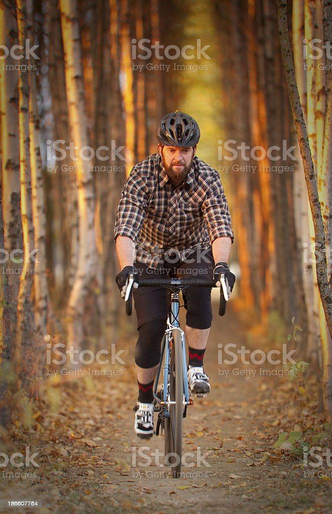 Bearded guy riding through tunnel on cyclocross course stock photo