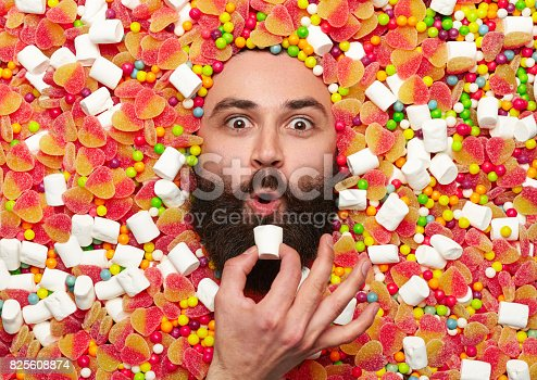 Bearded amazed guy holding marshmallow surrounded with jellies, candies and marshmallows.