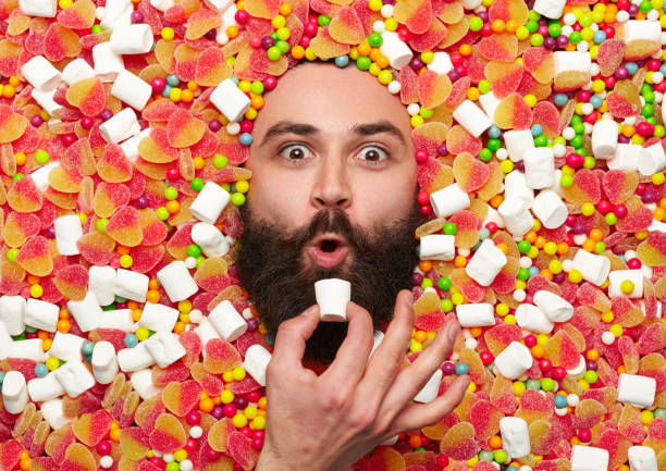 bearded guy surrounded with sweet stuff - bizarre stock pictures, royalty-free photos & images