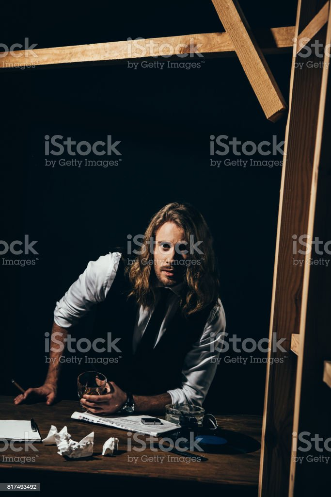 Bearded handsome long haired man in formal wear smoking cigar while holding glass of whisky and looking at camera stock photo
