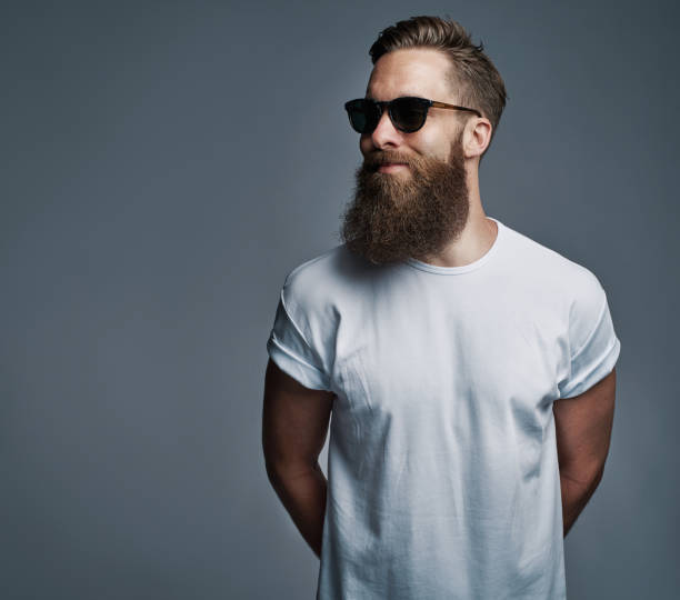 bearded handsome man with sunglasses looking over - beard stock pictures, royalty-free photos & images