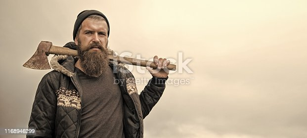 Handsome man hipster or guy with beard and moustache on serious face in hat and jacket holds rusty axe with wooden hilt outdoor against cloudy sky on natural background, copy space
