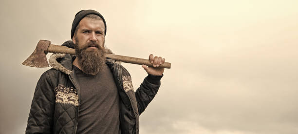 bearded handsome serious man with rusty axe against cloudy sky stock photo