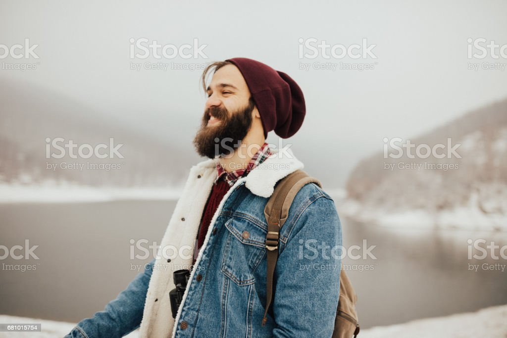 Bearded hiker wearing warm clothes and binoculars around his neck royalty-free stock photo