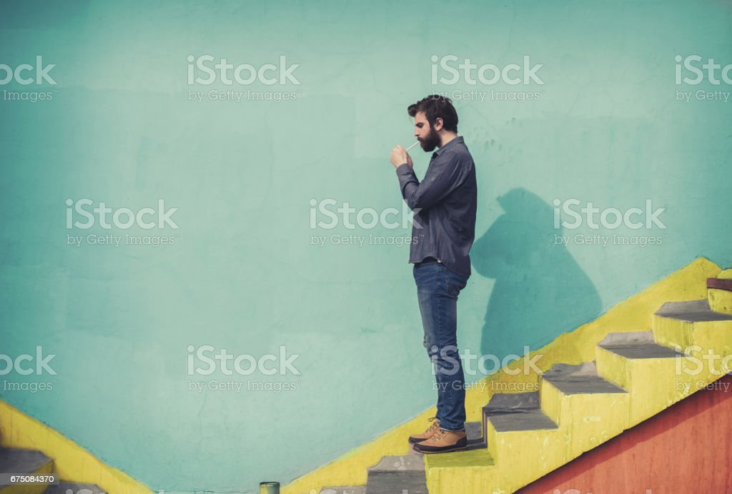Bearded hipster going down the stairs and lighting cigarette stock photo