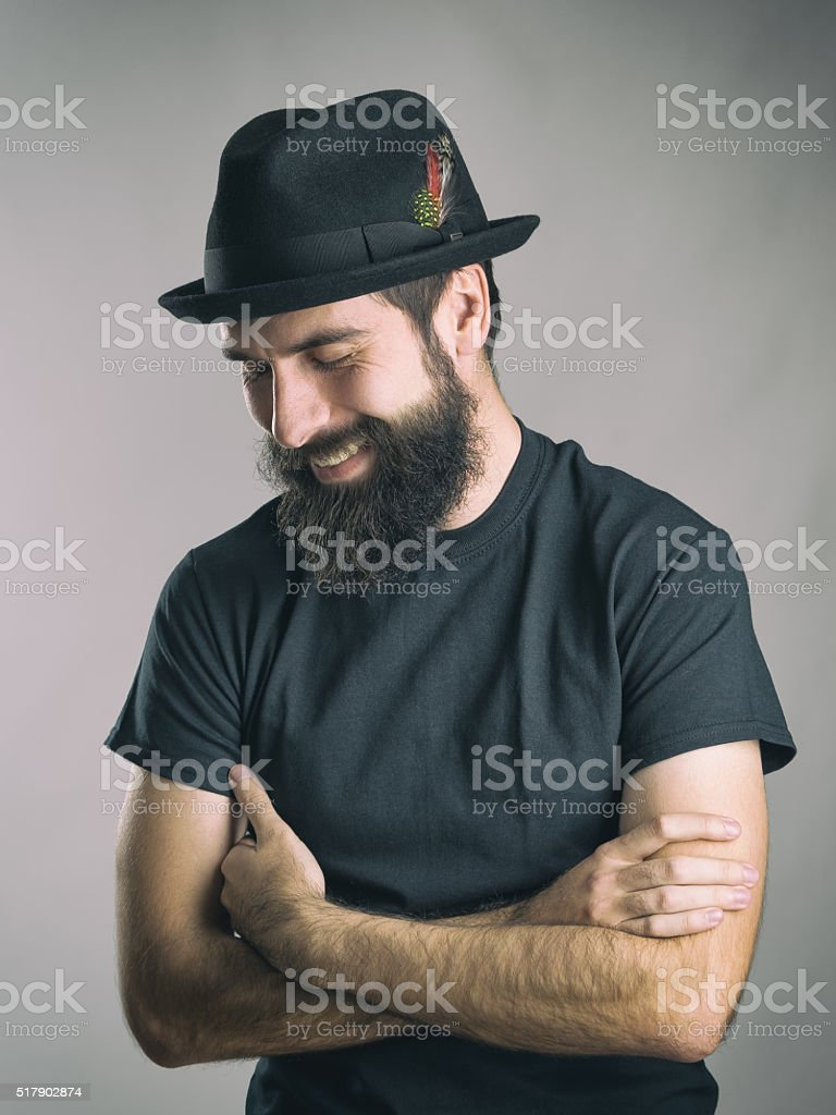Bearded hipster laughing spontaneous with closed eyes stock photo
