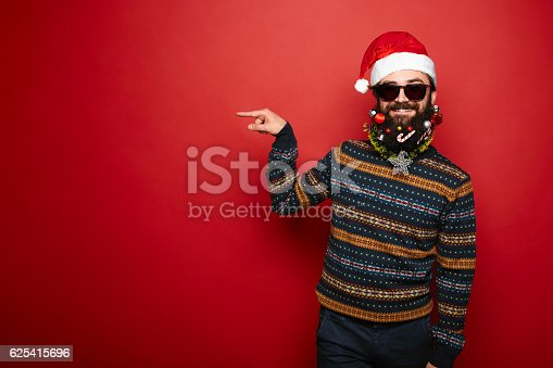 istock Bearded hipster man in santa hat gesturing to left 625415696