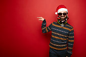 Bearded hipster man in santa hat gesturing to left