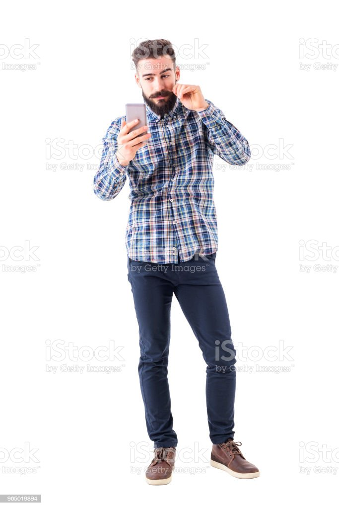 Bearded hipster man twirling mustache using mobile phone reflection...
