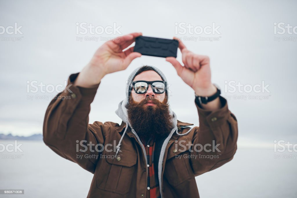 bearded hipster taking selfie in salt flats with retro tone stock photo