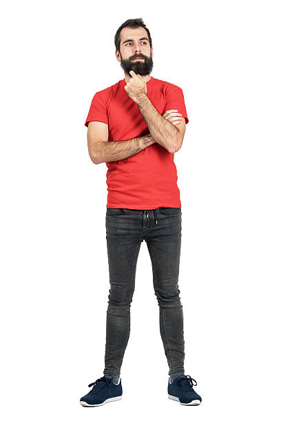 Bearded hipster thinking and touching his beard looking away. Bearded hipster thinking and touching his beard looking away. Full body length portrait isolated over white studio background. men in tight jeans stock pictures, royalty-free photos & images