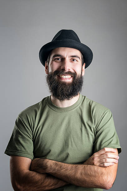 Bearded hipster wearing hat with upper lips piercing friendly laughing stock photo