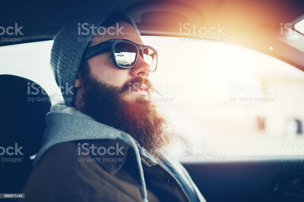 bearded hipster wearing sunglasses inside car stock photo