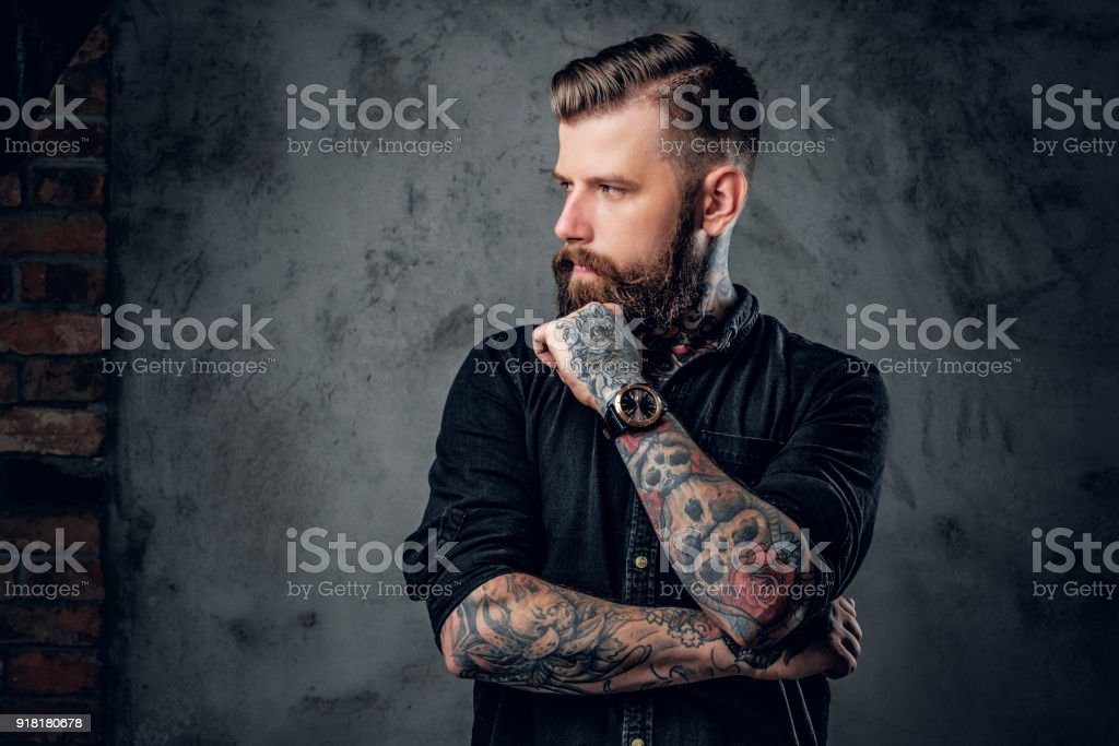 Bearded hipster with tattooe on his arms. stock photo