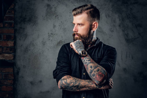 Bearded hipster with tattooe on his arms. - foto stock