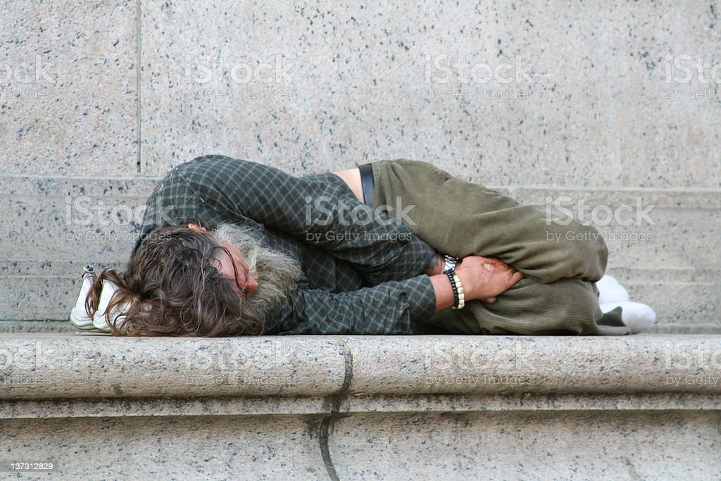 A bearded homeless man laying down on a stone ledge stock photo