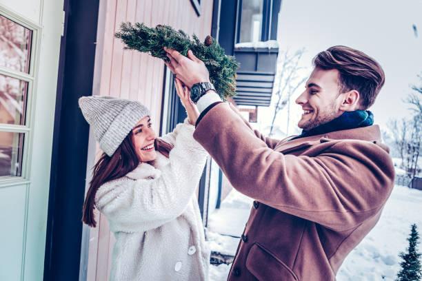 bärtiger mann setzen weihnachtskranz oh kopf seiner frau - buchstabentür kränze stock-fotos und bilder