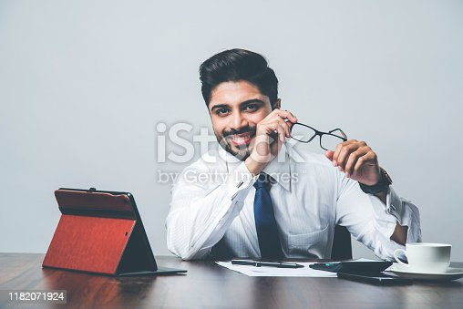 istock Bearded Indian Businessman accounting while sitting at desk / table in office 1182071924