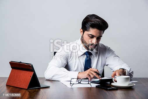 istock Bearded Indian Businessman accounting while sitting at desk / table in office 1182180885