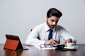 Bearded Indian Businessman accounting while sitting at desk / table in office