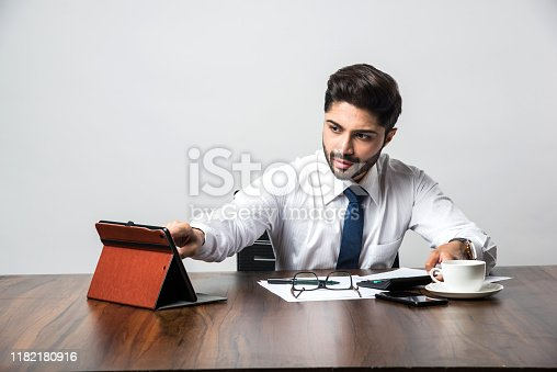 istock Bearded Indian Businessman accounting while sitting at desk / table in office 1182180916