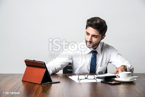 istock Bearded Indian Businessman accounting while sitting at desk / table in office 1182180940