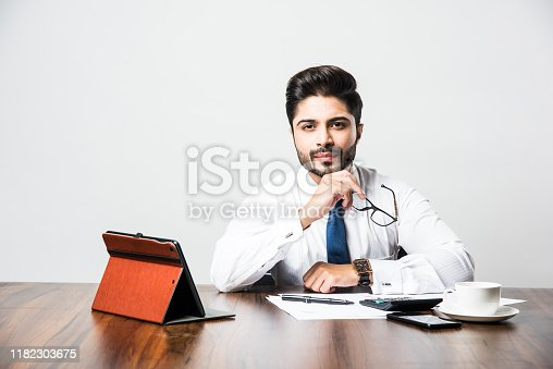 istock Bearded Indian Businessman accounting while sitting at desk / table in office 1182303675