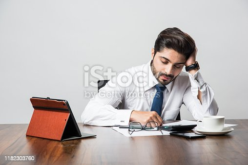 istock Bearded Indian Businessman accounting while sitting at desk / table in office 1182303760