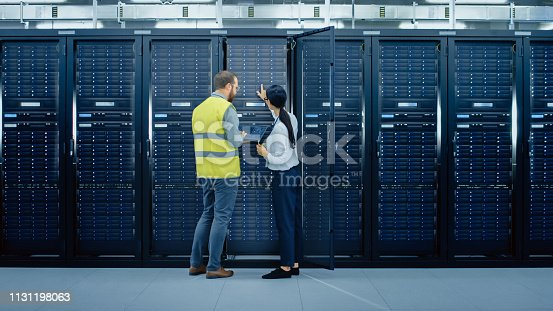 1131198396istockphoto Bearded IT Admin in Glasses and High Visibility Vest with a Laptop Computer and Young Technician Colleague Talking in Data Center while Standing Next to Server Racks. Running Diagnostics or Maintenance. 1131198063