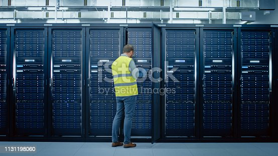 1131208605istockphoto Bearded IT Administrator in High Visibility Vest is Opening the Door to the Server Rack. He's Working on Laptop in Data Center while Standing Before Them. Running Diagnostics or Doing Maintenance Work. 1131198060