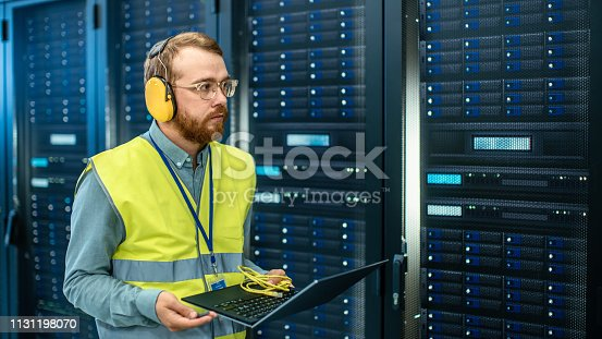 899720520 istock photo Bearded IT Specialist in Glasses and Headphones, wearing High Visibility Vest is Working on Laptop in Data Center Next to Server Racks. Running Diagnostics or Doing Maintenance Work. 1131198070