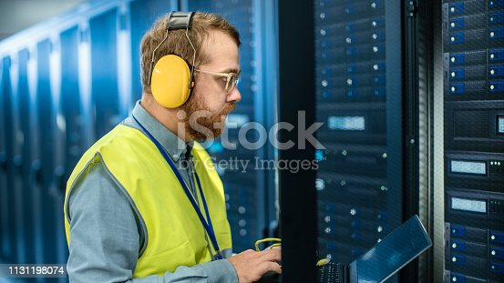 899720520istockphoto Bearded IT Specialist in Glasses and Headphones, wearing High Visibility Vest is Working on Laptop in Data Center Next to Server Racks. Running Diagnostics or Doing Maintenance Work. 1131198074