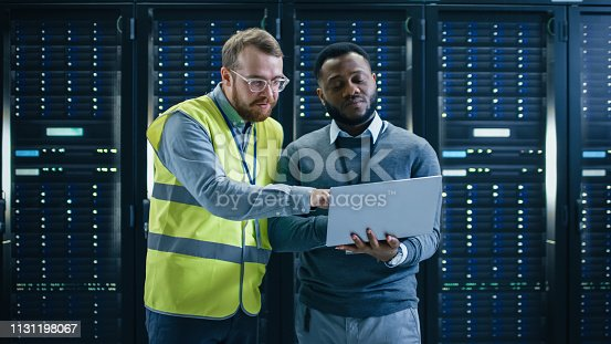 1131198396istockphoto Bearded IT Specialist in Glasses and High Visibility Vest and Black Technician Colleague with a Laptop Computer Talking in Data Center while Standing Next to Server Racks. Running Diagnostics or Maintenance. 1131198067