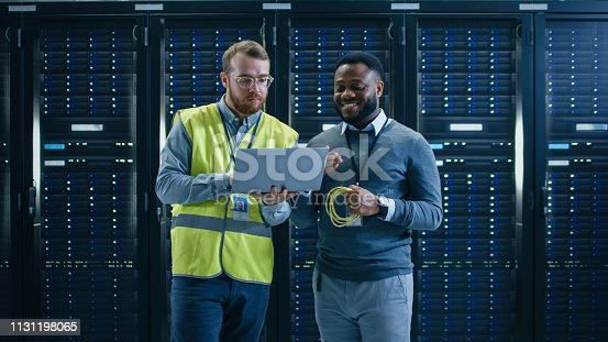 1131198396istockphoto Bearded IT Specialist in Glasses and High Visibility Vest with a Laptop Computer and Black Technician Colleague Talking in Data Center while Standing Next to Server Racks. Running Diagnostics or Maintenance. 1131198065
