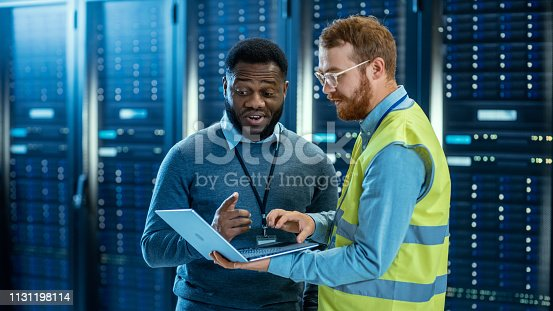 1131198396 istock photo Bearded IT Specialist in Glasses and High Visibility Vest with a Laptop Computer and Black Technician Colleague Talking in Data Center while Standing Next to Server Racks. Running Diagnostics. 1131198114