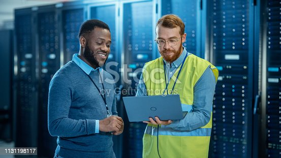 1131198396 istock photo Bearded IT Specialist in Glasses and High Visibility Vest with a Laptop Computer and Black Technician Colleague Talking in Data Center while Standing Next to Server Racks. Running Diagnostics. 1131198117
