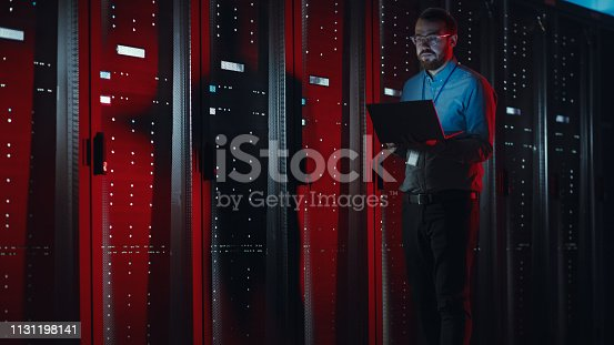 istock Bearded IT Specialist in Glasses is Working on Laptop in Data Center while Standing Near Server Rack. Running Diagnostics, Doing Maintenance Work. Emergency Red Light from Side Illuminating Specialist 1131198141
