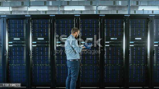 1131208605 istock photo Bearded IT Specialist in Glasses is Working on Laptop in Data Center while Standing Before Server Rack. Running Diagnostics or Doing Maintenance Work. 1131198272