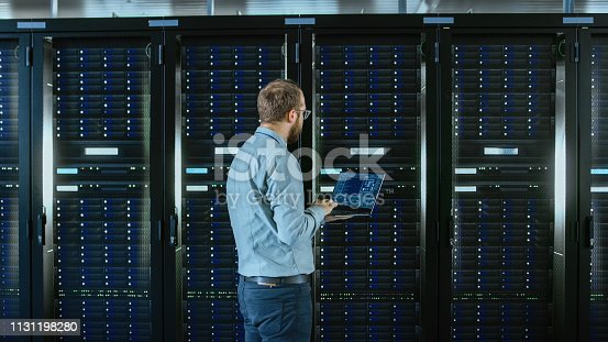 1131208605 istock photo Bearded IT Specialist in Glasses is Working on Laptop in Data Center while Standing Before Server Rack. Running Diagnostics or Doing Maintenance Work. 1131198280