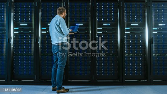 1131208605 istock photo Bearded IT Specialist in Glasses is Working on Laptop in Data Center while Standing Before Server Rack. Running Diagnostics or Doing Maintenance Work. 1131198292