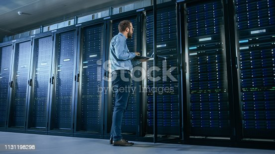 1131208605 istock photo Bearded IT Specialist in Glasses is Working on Laptop in Data Center while Standing Before Server Rack. Running Diagnostics or Doing Maintenance Work. 1131198298